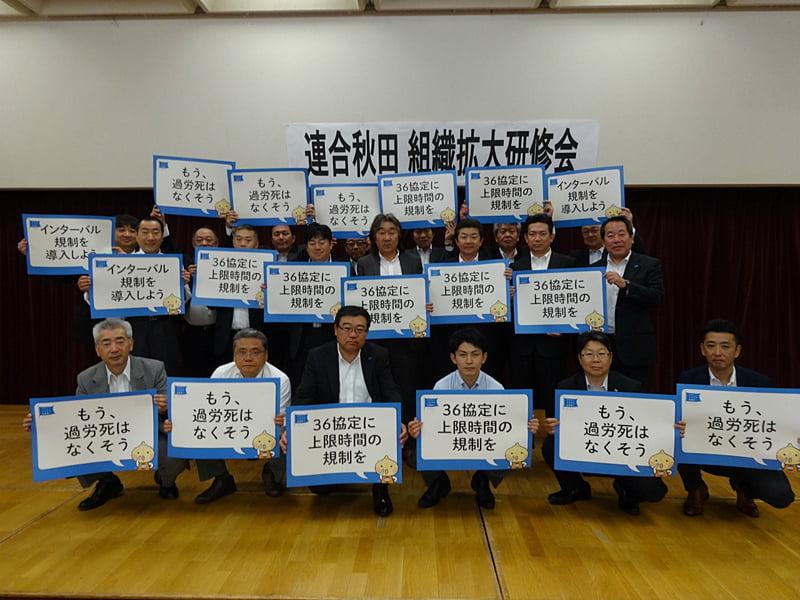 写真:長時間労働是正のボードを掲げる参加者